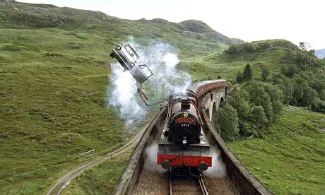 Harry Potter dangles from the Weasley car chasing the Hogwarts Express along Glenfinnan viaduct